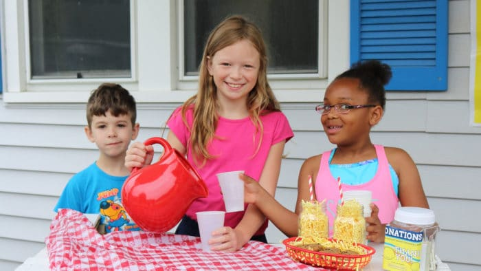 Two girls and a boy at a lemonade stand