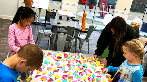 Children and an adult at a table with a blanket on it