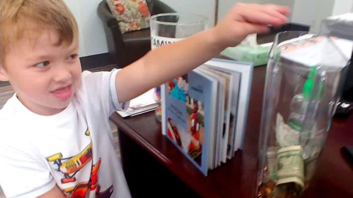 Boy putting money into a jar