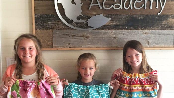 Three girls holding up dresses