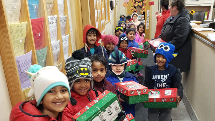 Children in winter coats with Christmas presents