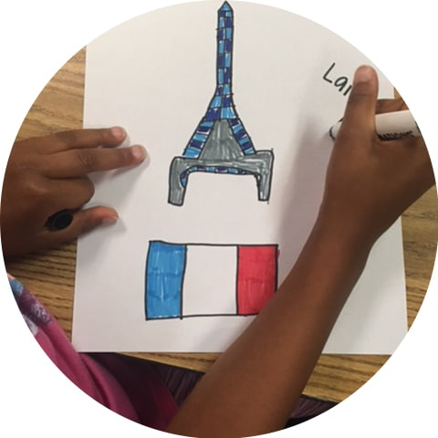 A child holds a drawing of the Eiffel Tower