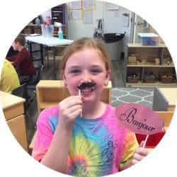 Child holds up fake moustache