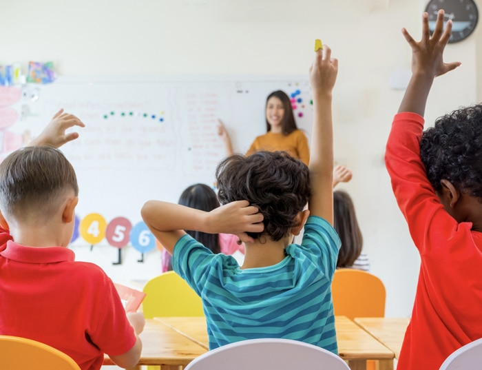 Children raising their hands in classroom